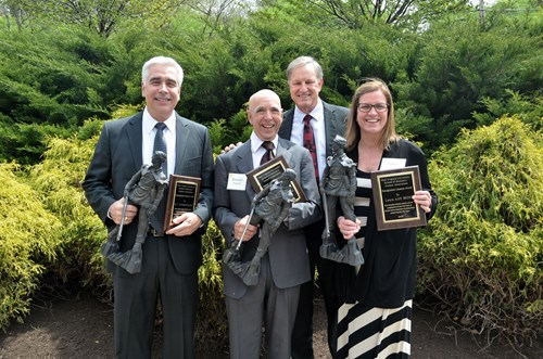 Alumni association president poses with distinguished alumni award winners.