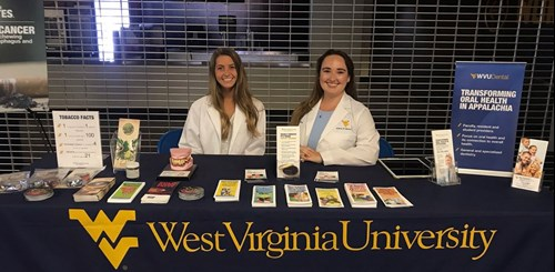Claire Frank, dental hygiene student, and Laura Settles, DDS student, present nicotine addiction awareness.